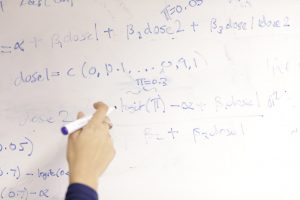 Decorative image of BSU member writing on white board